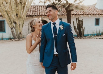 photo of groom wearing a blue suit laughing and holding hands with a bride in white wedding dress