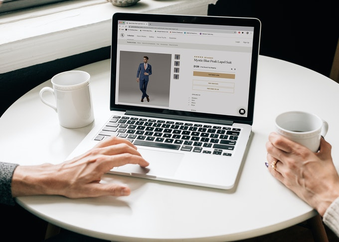 photo of two people's hands browsing generation tux site while enjoying coffee