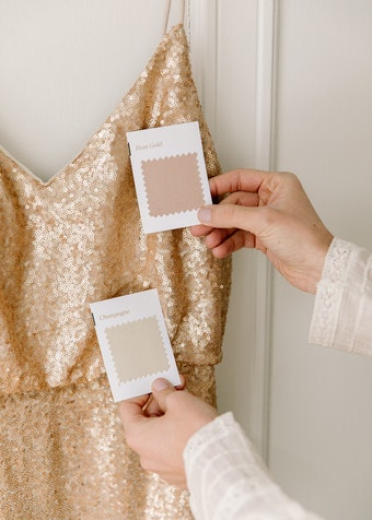 photo of woman's hands comparing suit swatch colors to gold bridesmaid dress