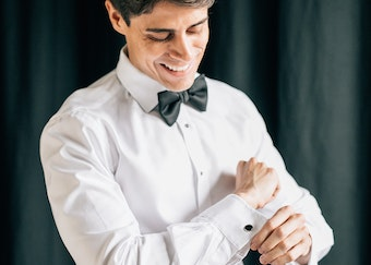 photo of man adjusting cufflinks while putting on a black tuxedo
