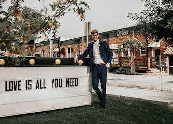 photo of a red haired man in a navy suit standing next to a sign