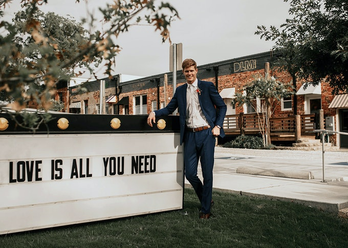 photo of a red haired man in a navy suit standing next to a love is all you need sign
