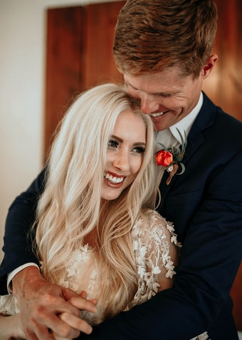 photo of a groom wearing a black tuxedo holding his blonde bride