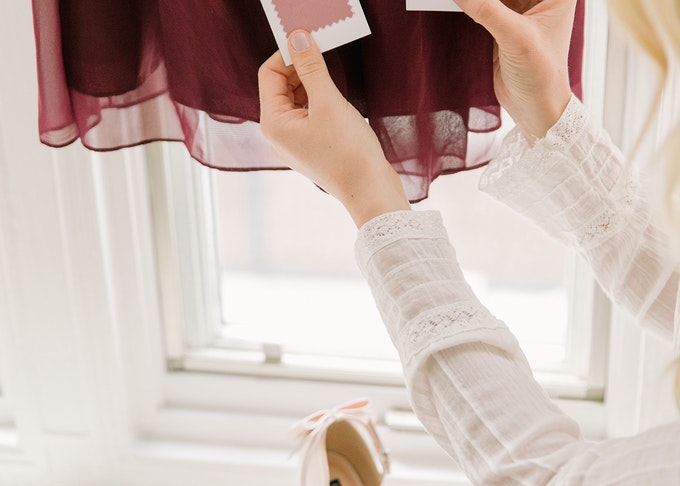 photo of a woman's hands holding tuxedo fabric accessory swatches comparing to bridesmaid dress