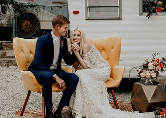 photo of a groom in a blue suit and a bride in wedding dress sitting on a yellow couch