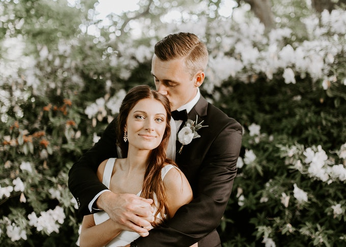 photo of a groom in a black tuxedo hugging his bride surrounded by white flowers