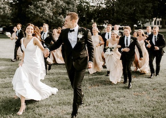 photo of groom holding bride's hand while running outside with wedding party behind