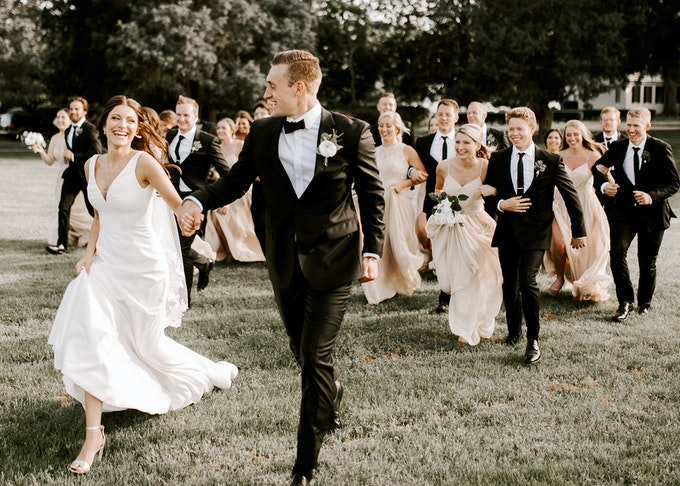 photo of groom in a black tuxedo holding bride's hand while running outside with wedding party behind