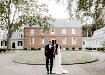 photo of a groom in a tux next to a bride in wedding dress while outdoors in front of a house