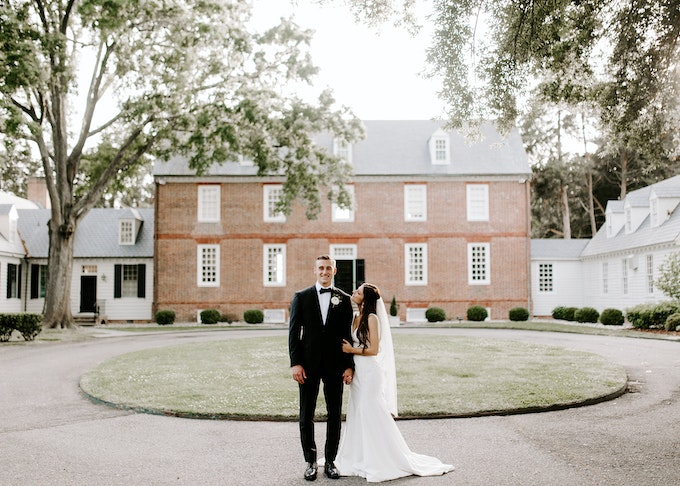 photo of a groom in a black tuxedo next to a bride in wedding dress while outdoors in front of a house