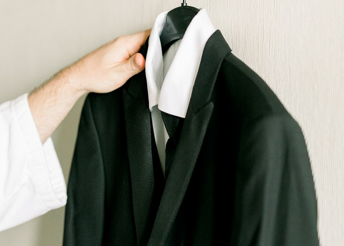photo of a hand reaching for a black tuxedo hanging on the wall