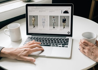 photo of a two people's hands browsing the generation tux website while enjoying cups of coffee
