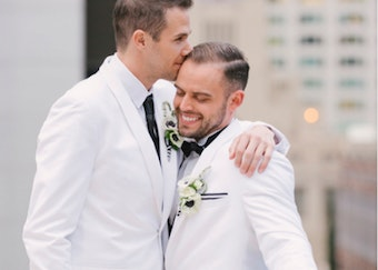photo of gay couple wearing white tuxedos on a balcony during a wedding