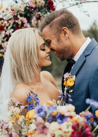 photo of a groom and bride during a wedding ceremony surrounded by flowers
