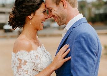photo of brunette bride in her wedding dress embracing her husband in a sky blue tuxedo
