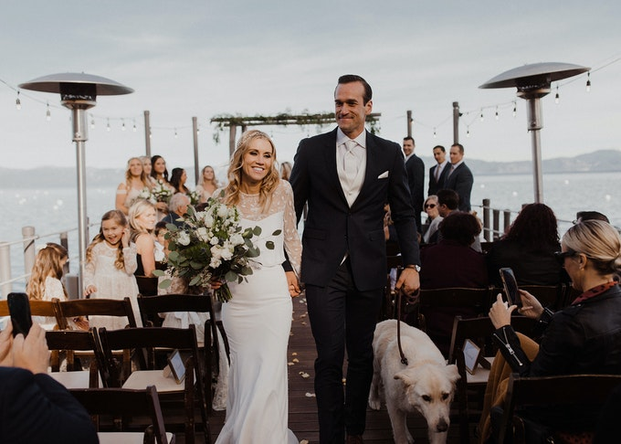 photo of a groom and bride walking down the aisle at the end of a wedding ceremony wearing a tuxedo and a wedding dress