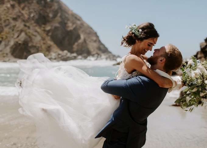 photo of bride embracing groom while on a beach in california
