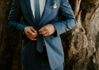 photo of man's torso while adjusting the buttons on his blue suit