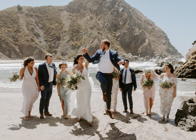candid photo of groom and bride with groomsmen and bridesmaids while on the beach