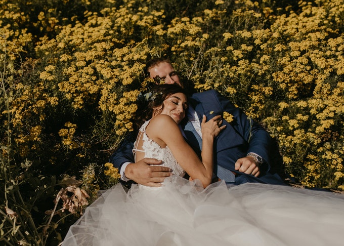 photo of groom and bride laying down together in a field of sunflowers