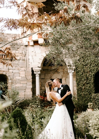 photo of a bride and groom kissing while outdoors in a lush garden setting