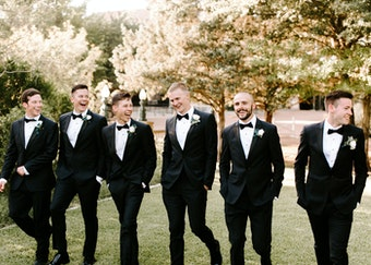 photo of groomsmen in black tuxedos walking side by side and laughing