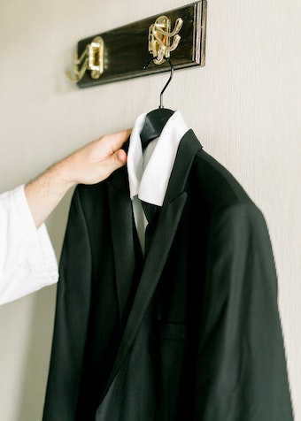 photo of a hand reaching for a black tuxedo hanging on a wall