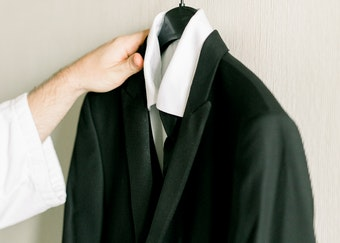photo of a woman's hand reaching for a black tuxedo hanging on the wall