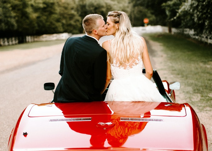 photo shot from behind of a groom and bride kissing while sitting in an old red corvette
