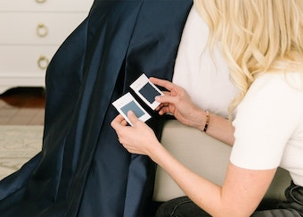photo of a blonde woman comparing color swatches to a blue bridesmaid dress