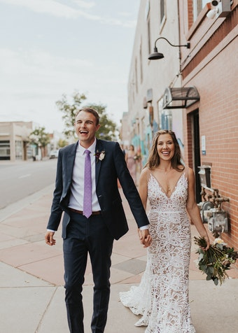 photo of a groom and bride walking outside and smiling while holding hands