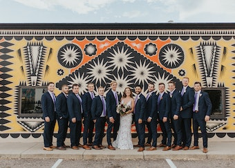 photo of a wedding party all dressed up and posing together in front of a mural