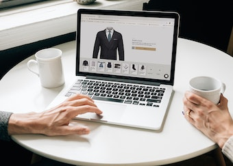 photo of two hands browsing the generation tux website while drinking coffee