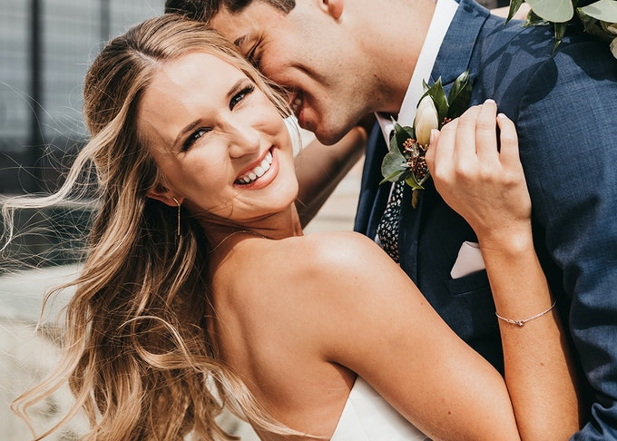 photo of groom and bride embracing during wedding while the bride smiles into the camera