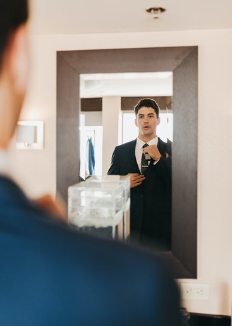photo of a man wearing a tuxedo straightening his tie while looking into the mirror