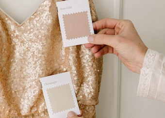 photo of a woman's hands comparing tuxedo color swatches to a gold bridesmaid dress