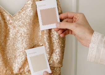 photo of a woman's hands holding gold and pick suit color swatches next to dress