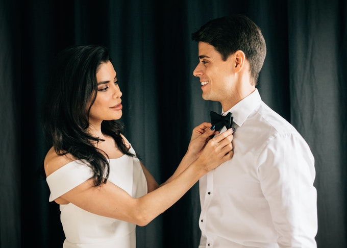 photo of a woman in a white dress adjusting the bowtie of a man in a tuxedo