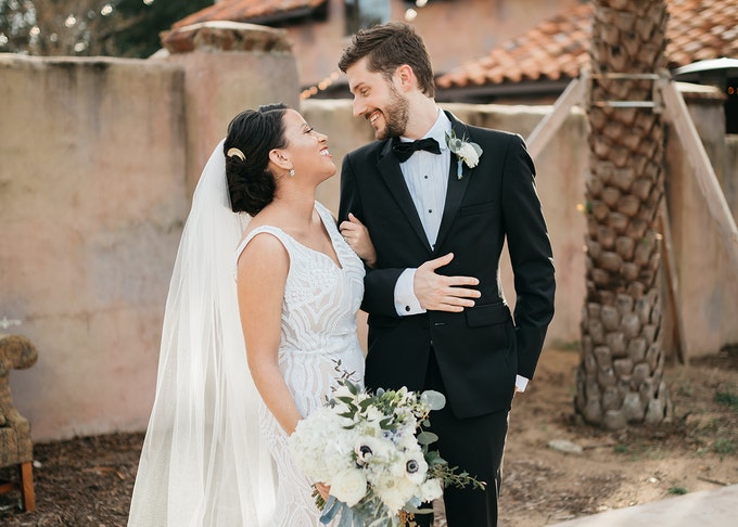 photo of bride holding flowers and groom while outdoors smiling into each others' eyes