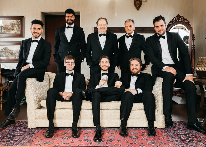 photo of groomsmen wearing black tuxedos and posing on a couch together