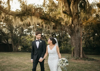 candid photo of a bride and groom underneath a willow tree holding hands and walking