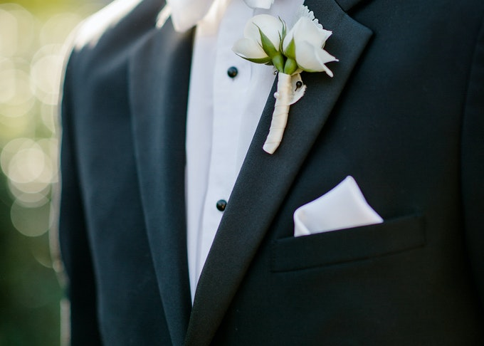closeup photo of a man wearing a tuxedo and a white pocket square