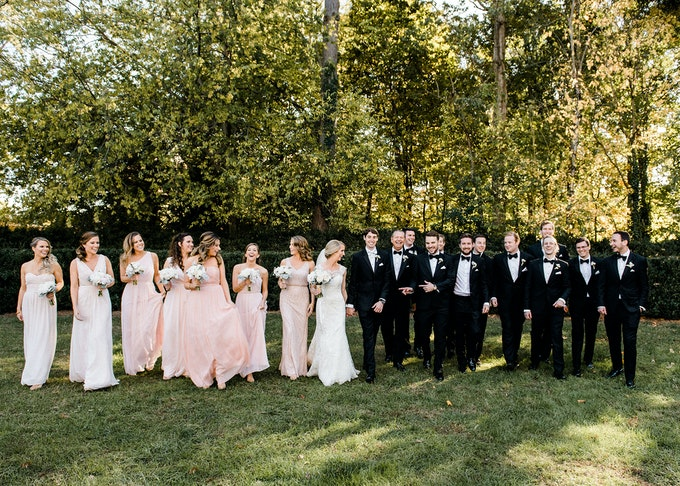 outdoor photo of a wedding party, groomsmen wearing black tuxedos, bridesmaids in rose pink