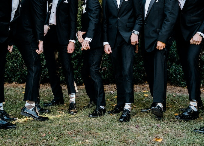 photo of groomsmen showing off their matching black trousers and black shoes