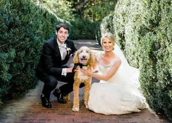photo of a groom and bride outside crouching and smiling next to a poodle