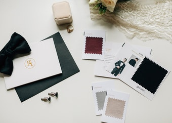 photo of tuxedo color swatches next to cufflinks, a black bowtie, and a card