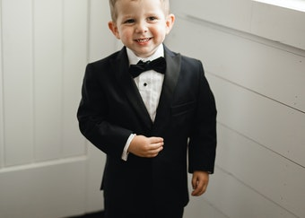 photo of a young boy wearing a black tuxedo and smiling