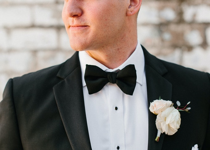 photo of a man wearing a black tuxedo and black bowtie looking away from the camera