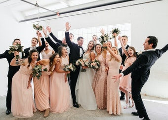 photo of a wedding party, bridesmaids wearing rose and groomsmen wearing black tuxedos