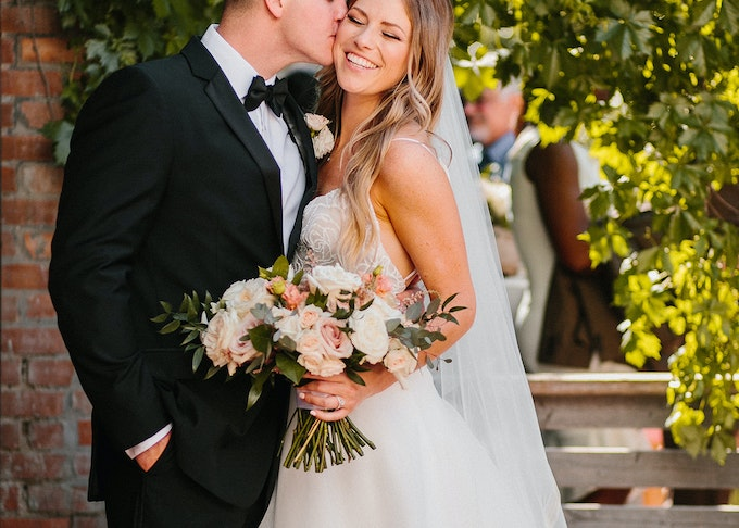 photo of a young groom in a black tuxedo kissing a young bride who's holding a bouquet of flowers